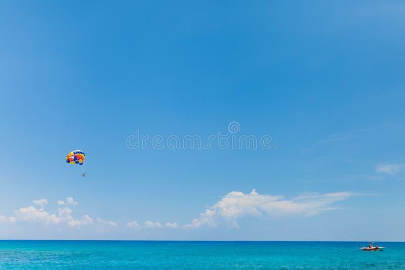 Gente que vuela en un paracaídas colorido remolcado por un barco de motor imagen de archivo libre de regalías