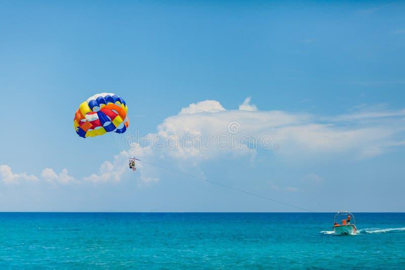 Gente que vuela en un paracaídas colorido remolcado por un barco de motor fotos de archivo libres de regalías