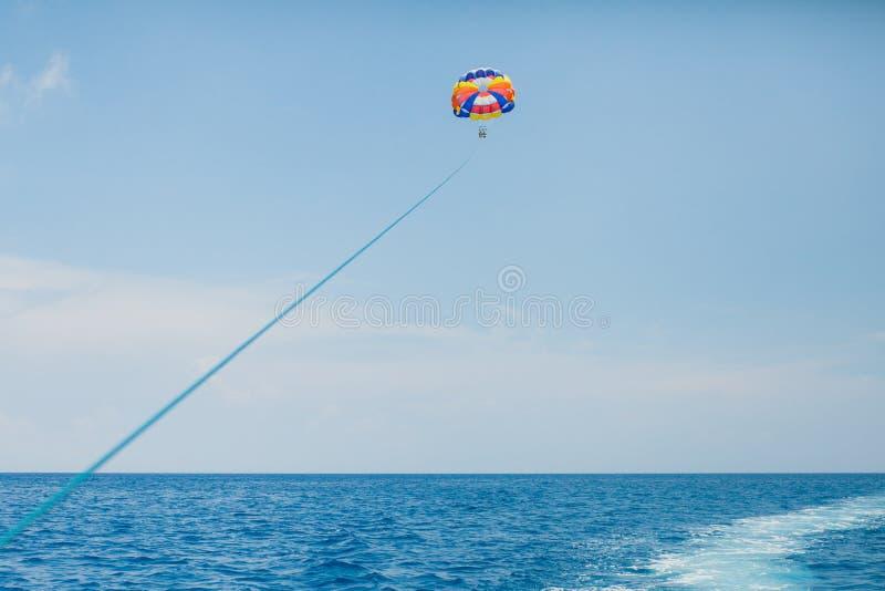 Gente que vuela en un paracaídas colorido remolcado por un barco de motor imágenes de archivo libres de regalías