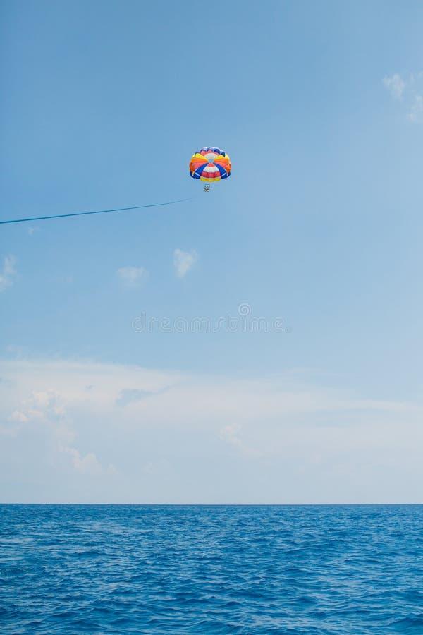 Gente que vuela en un paracaídas colorido remolcado por un barco de motor foto de archivo libre de regalías