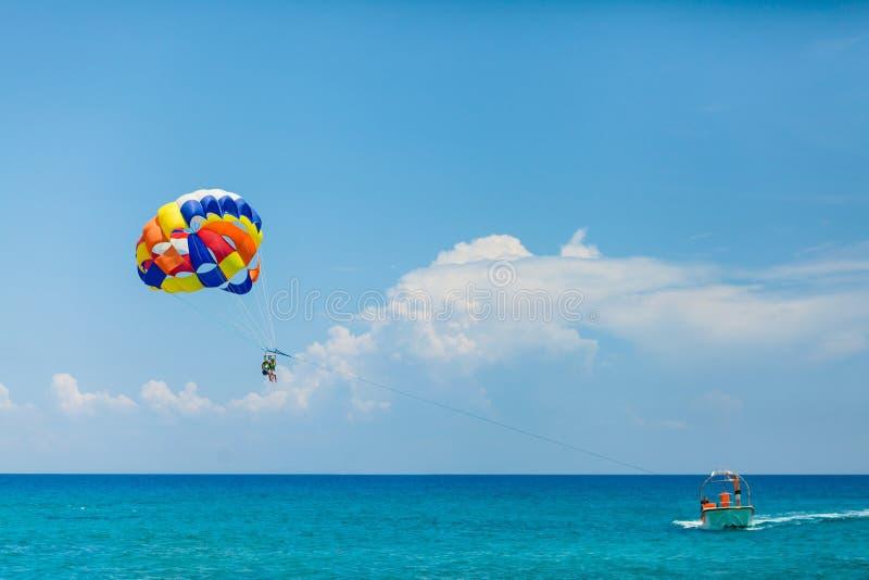Gente que vuela en un paracaídas colorido remolcado por un barco de motor imagen de archivo