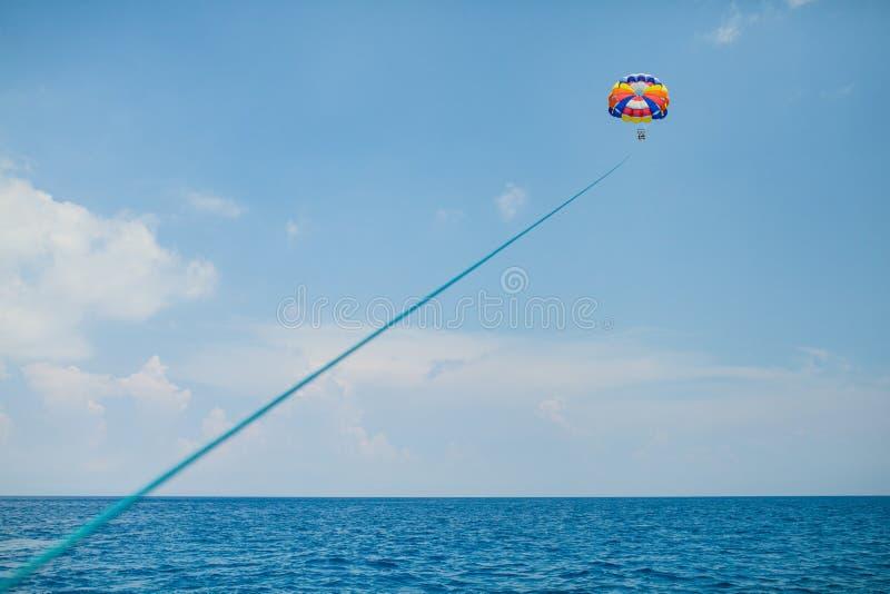 Gente que vuela en un paracaídas colorido remolcado por un barco de motor fotos de archivo