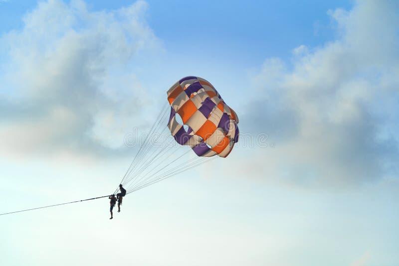 Gente que vuela en un paracaídas o un parasail colorido así como el cielo azul y las nubes en concepto de la libertad y del viaje imagen de archivo