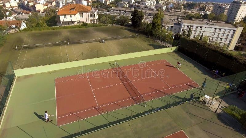 Gente rica que juega a tenis en la corte de lujo, pasatiempos, fin de semana del deporte fotografía de archivo libre de regalías