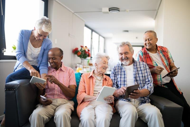 Gente senior felice che per mezzo dei computer della compressa fotografia stock libera da diritti