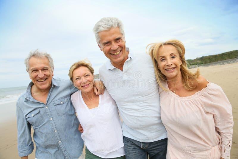 Gente senior felice d'avanguardia che cammina sulla spiaggia immagini stock libere da diritti