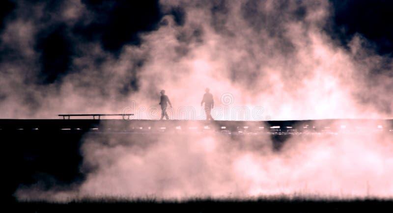Gente silueteada contra la niebla imagenes de archivo