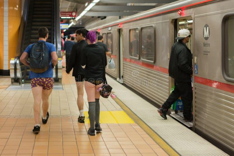 Gente sin los pantalones que llegan en la estación de metro durante imagen de archivo libre de regalías