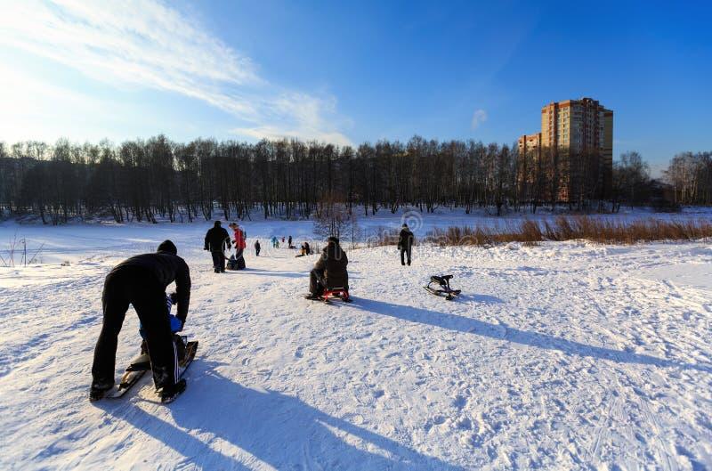Gente sledding abajo del riverbank del río de Pekhorka en un día de invierno soleado Ciudad de Balashikha, región de Moscú, Rusia imagen de archivo