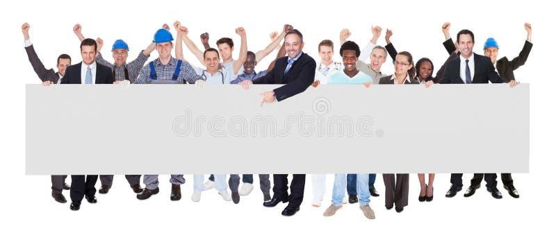 Gente sonriente con los diversos empleos que sostienen la cartelera en blanco imagen de archivo libre de regalías
