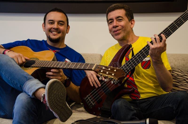 Gente sonriente joven que toca las guitarras que se sientan en un sofá imagen de archivo libre de regalías