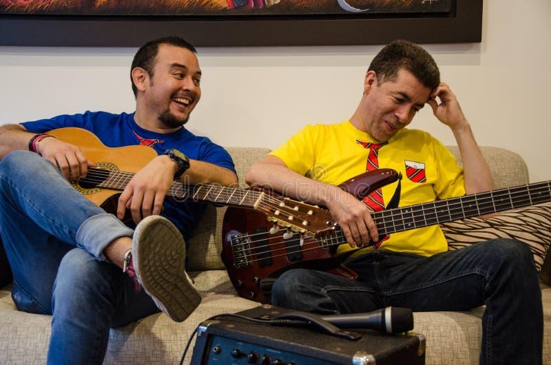 Gente sonriente joven que toca las guitarras que se sientan en un sofá foto de archivo