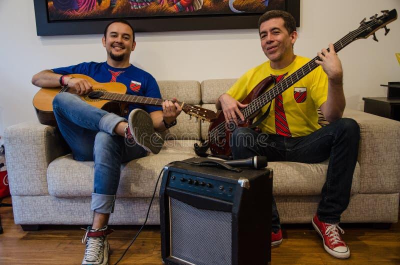 Gente sonriente joven que toca las guitarras que se sientan en un sofá en casa imagen de archivo libre de regalías