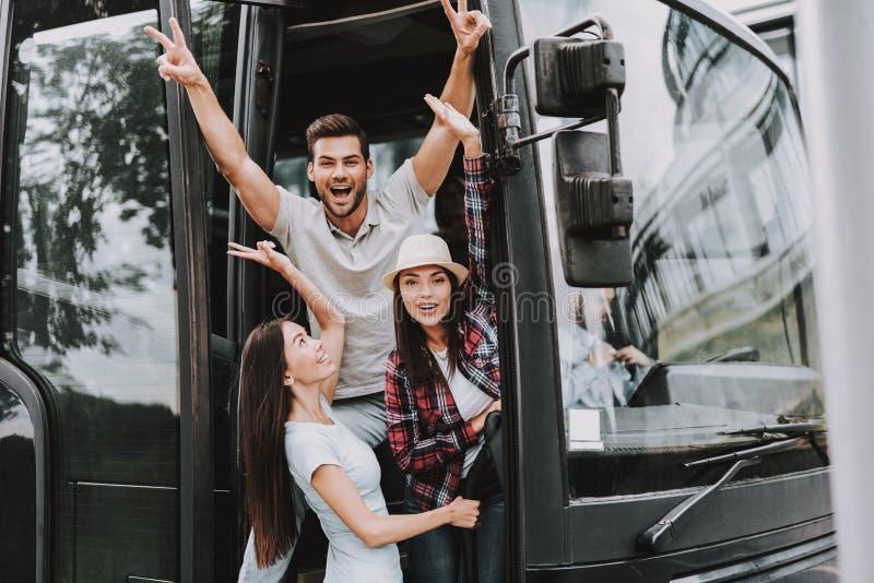 Gente sonriente joven que viaja en el autobús turístico fotografía de archivo libre de regalías