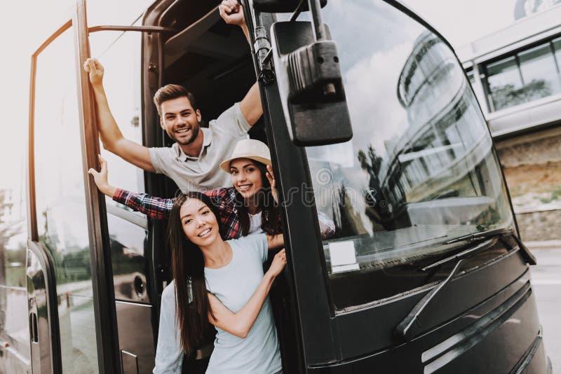 Gente sonriente joven que viaja en el autobús turístico foto de archivo libre de regalías