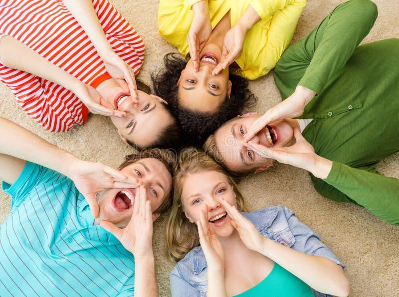Gente sonriente que se acuesta en piso y que grita fotos de archivo libres de regalías