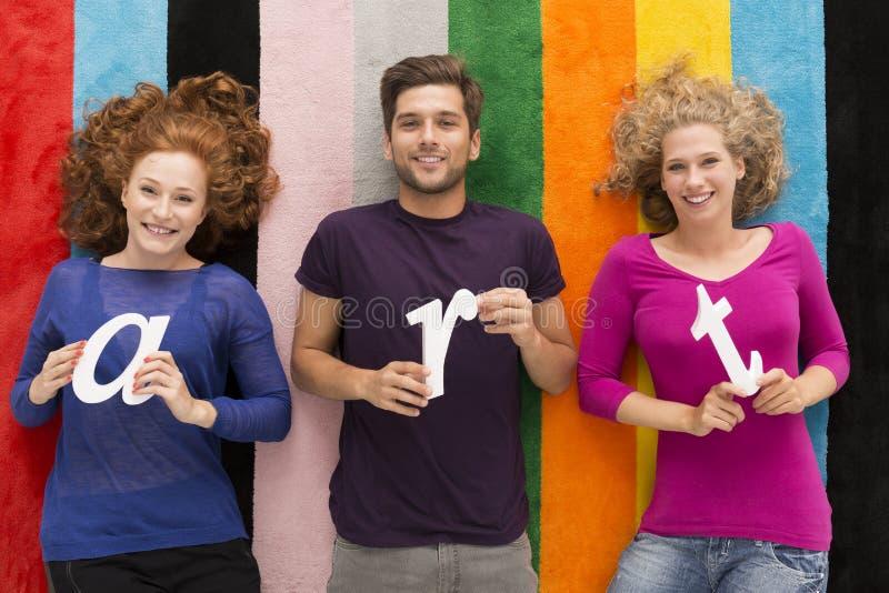 Gente sorridente che si trova su un tappeto fotografia stock libera da diritti