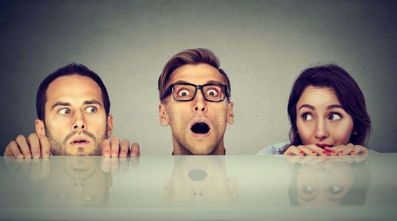 Gente spaventata due uomini e una donna che si nasconde dando una occhiata alla forma sotto la tavola fotografia stock
