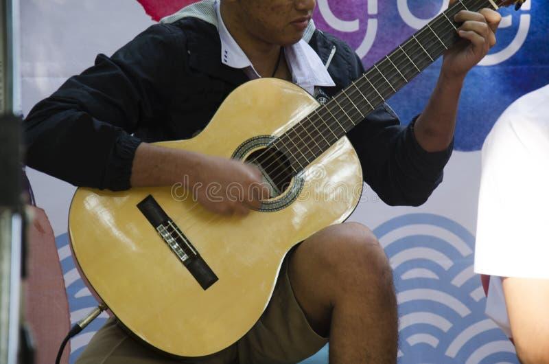 Gente tailandesa del niño que toca la guitarra acústica para el PE de los viajeros de la demostración foto de archivo libre de regalías