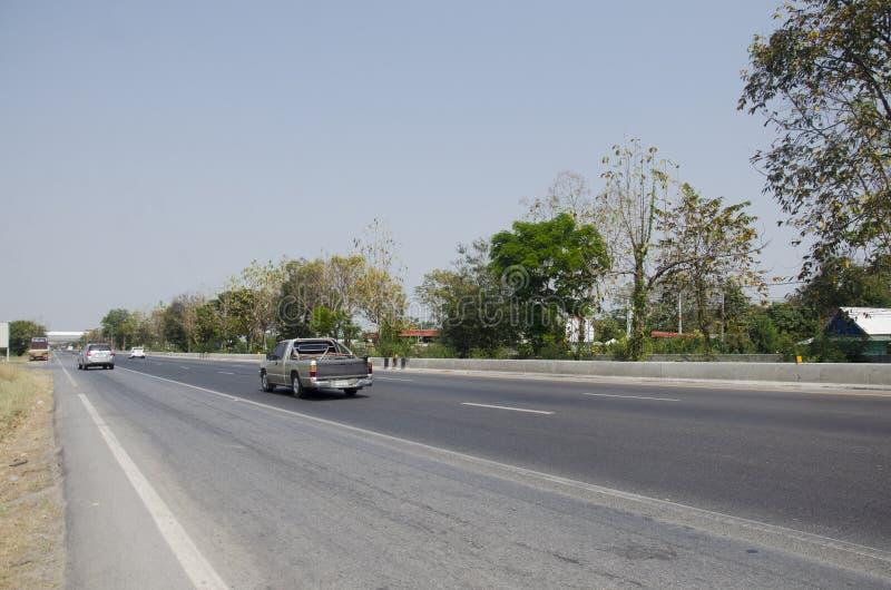 Gente tailandesa que conduce el coche en la calle del asfalto con el camino del tráfico en la carretera asiática en Ang Thong, Ta foto de archivo