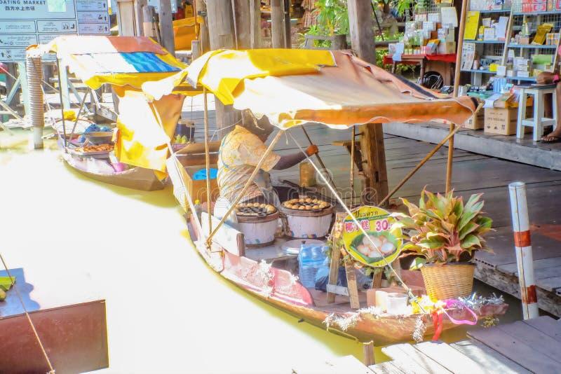 Gente tailandesa Unacquainted que vende la torta de coco famosa tailandesa de la comida de la calle en el barco en mercado flotan imagen de archivo