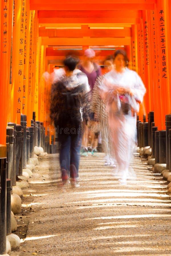 Gente Torii borroso que camina de la capilla de Fushimi Inari fotos de archivo