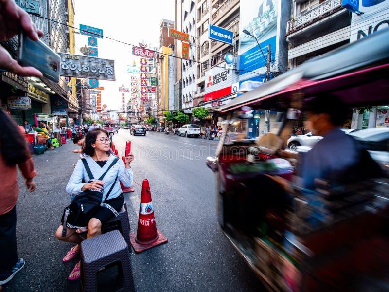 Gente turistica che si siede accanto alla strada e che per mezzo del telefono cellulare per la foto della presa con l'automobile  fotografie stock