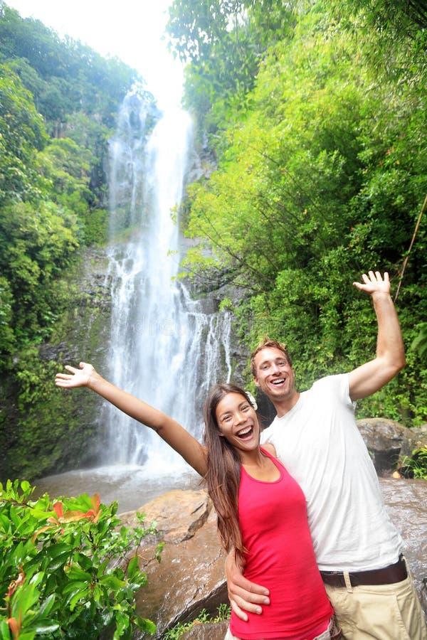 Gente turistica delle Hawai felice dalla cascata fotografie stock libere da diritti