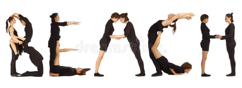 Gente vestida negro que forma palabra de la PLAYA imágenes de archivo libres de regalías