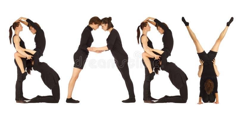 Gente vestida negro que forma palabra del BEBÉ imagenes de archivo