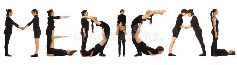 Gente vestida negro que forma palabra MÉDICA imagen de archivo libre de regalías