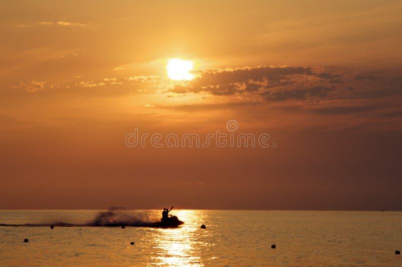 Gente watercrafting durante puesta del sol en la costa de Tropea Calabria Italia imagen de archivo