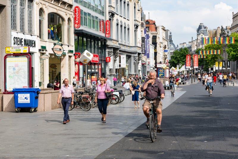 Gente y ciclistas en la calle principal de las compras de Amberes, Bélgica imagenes de archivo