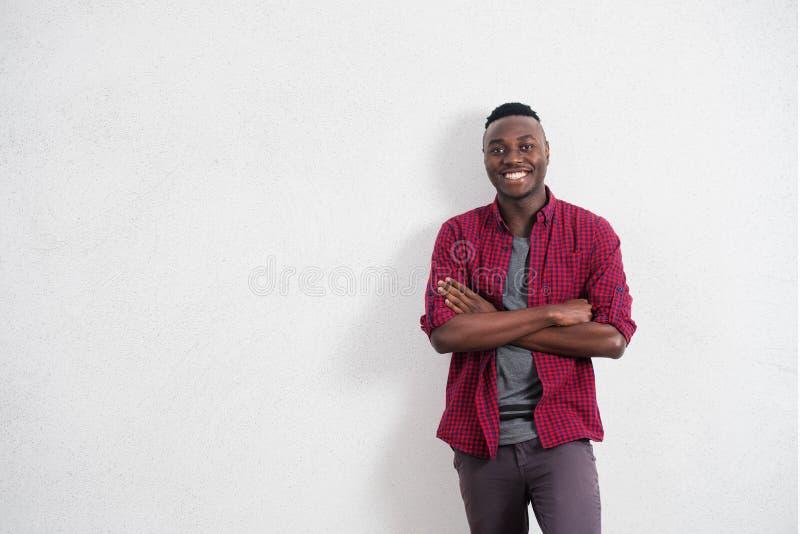 Gente y concepto de la forma de vida Retrato del varón africano joven feliz y positivo en buen humor, camisa roja que lleva imagen de archivo