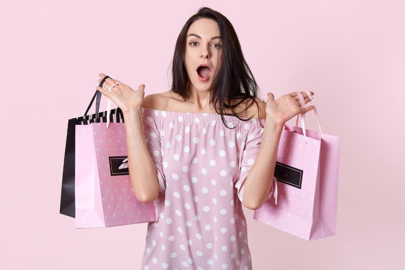Gente y concepto del choque Shopaholic femenino sorprendida vestida en vestido elegante, sostiene bolsos en dos manos, olvida la  foto de archivo libre de regalías