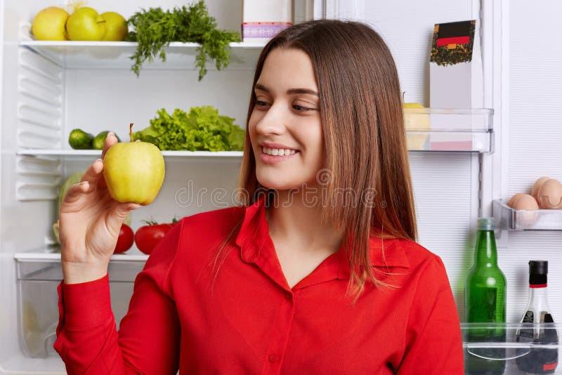 Gente y concepto sano de la nutrición La mujer joven adorable con la expresión alegre, manzana fresca verde de los controles, dem fotografía de archivo