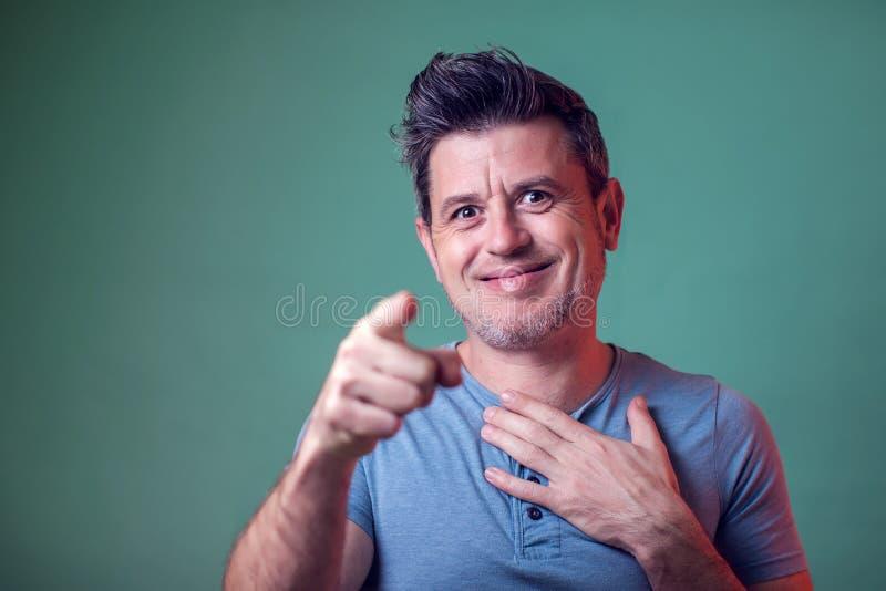 Gente y emociones - un retrato de las sonrisas y de los puntos del hombre con un finger en la cámara foto de archivo libre de regalías