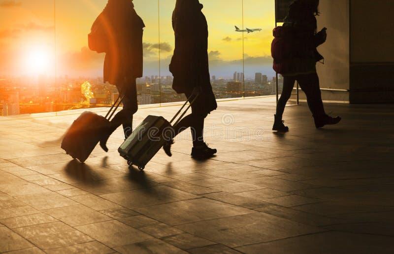 Gente y equipaje que viaja que caminan en buildin del terminal de aeropuerto foto de archivo