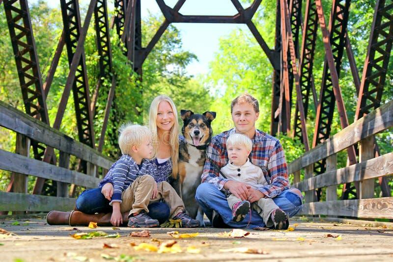 Gente y perro de la familia de cuatro miembros que se sientan en el puente en otoño imágenes de archivo libres de regalías