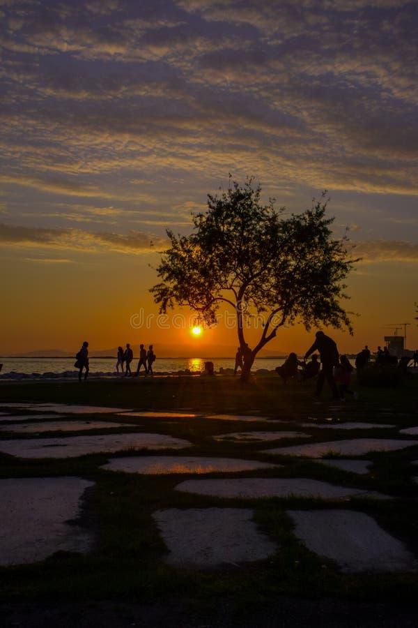 Gente y puesta del sol en la playa imagenes de archivo