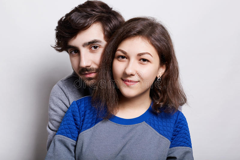 Gente y relaciones Pares jovenes que se colocan cerca de la pared blanca Un individuo del inconformista con la barba que se coloc imagen de archivo libre de regalías