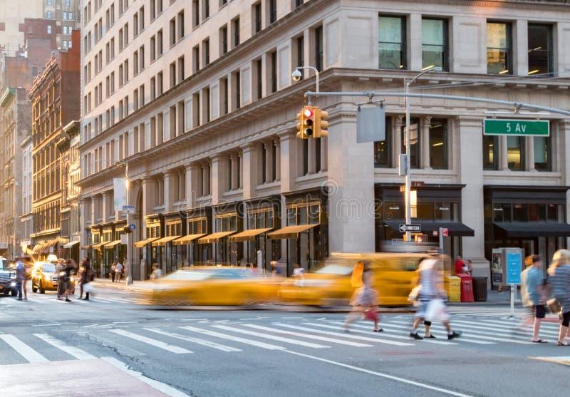 Gente y taxis en la intersección de Fifth Avenue y 23ro en New York City imagen de archivo libre de regalías