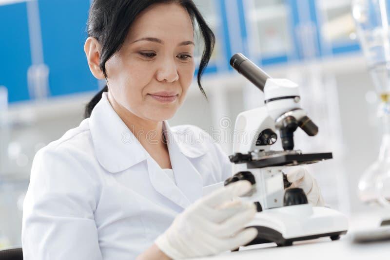 Gentil biologiste professionnel regardant la glissière de microscope image libre de droits