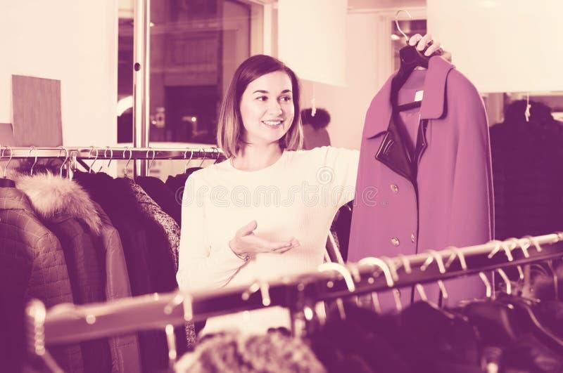 Gentil client féminin examinant le manteau de laine rouge photo stock