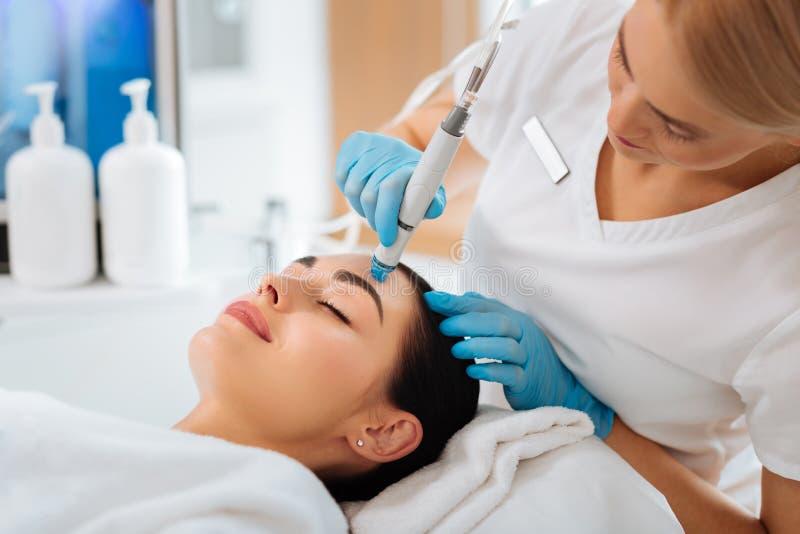 Gentil cosmetologist féminin professionnel étant au travail image stock