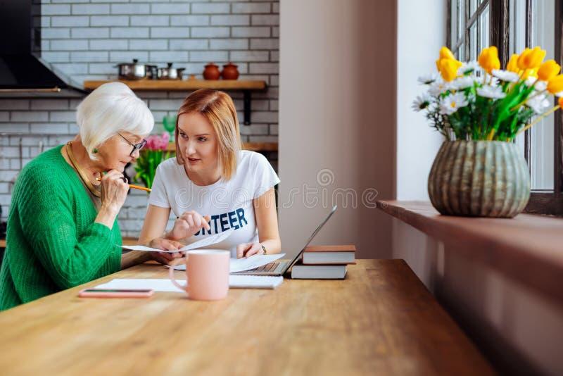 Gentil-en appeler à la femme agée de consultation des employés sociaux au sujet des documents financiers image libre de droits