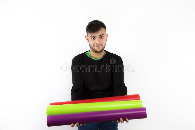 Gentil et moderne jeune travailleur de sourire avec la barbe tenant des petits pains de vinyle photos stock