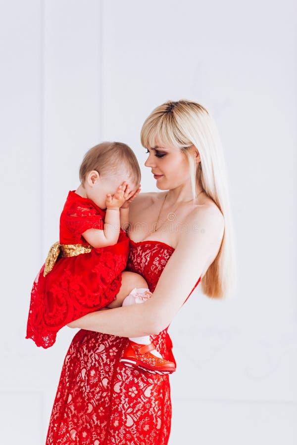 Gentil, famille, bonne photo de m?re et fille dans des robes rouges dans le studio Le jour et les filles de m?re photo stock