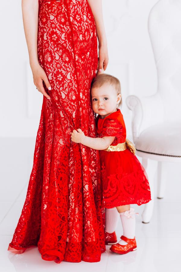Gentil, famille, bonne photo de m?re et fille dans des robes rouges dans le studio Le jour et les filles de m?re image stock