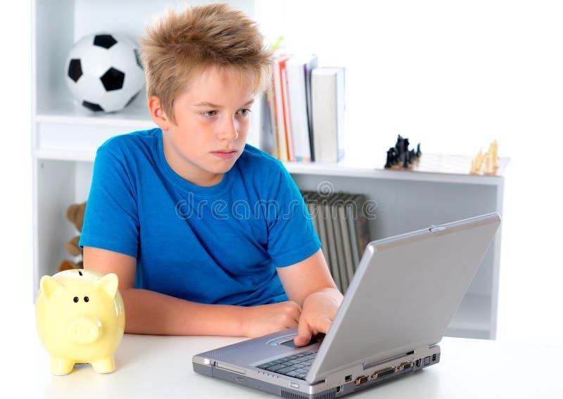 Gentil garçon avec l'ordinateur portable et la tirelire photo libre de droits